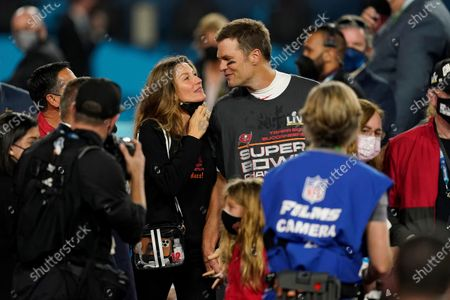 Tampa Bay Buccaneers quarterback Tom Brady walks with Gisele Bundchen on the field after the NFL Super Bowl 55 football game against the Kansas City Chiefs, in Tampa, Fla. The Tampa Bay Buccaneers defeated the Kansas City Chiefs 31-9