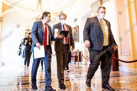 U.S. Senator Sherrod Brown (D-OH), flanked by U.S. Senator Brian Schatz (D-HI) and U.S. Senator Jon Tester (D-MT), walk to a press conference to discuss how work on President Biden's American Rescue Plan will continue during the Senate impeachment trial.