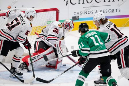 Chicago Blackhawks' Ian Mitchell (51) and Nikita Zadorov (16) help goaltender Kevin Lankinen (32) defend against a shot and pressure from Dallas Stars' Andrew Cogliano (11) in the first period of an NHL hockey game in Dallas