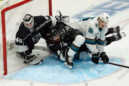 San Jose Sharks left wing Rudolfs Balcers (92) crashes in to Los Angeles Kings goaltender Calvin Petersen (40) and defenseman Drew Doughty (8) during the second period of an NHL hockey game, in Los Angeles