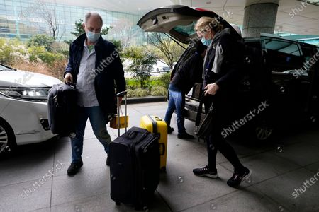 John Watson, left and Thea Koelsen Fischer of the World Health Organization team arrive at the VIP terminal of the airport to leave at the end of the WHO mission in Wuhan, China