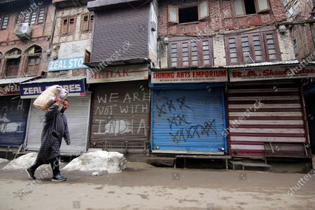 Stock Photo of A man walks past closed shops in Srinagar, Kashmir on February 09, 2021. Shops and business establishments remain closed in Srinagar on the 8th death anniversary of Afzal Guru who was secretly hanged in New Delhi's Tihar jail 0n February 09, 2031 for his alleged role in Indian parliament attack. (Photo by Faisal Khan/NurPhoto)