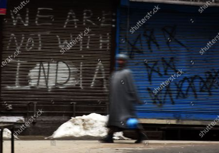 A man walks past a closed shop in Srinagar, Kashmir on February 09, 2021. Shops and business establishments remain closed in Srinagar on the 8th death anniversary of Afzal Guru who was secretly hanged in New Delhi's Tihar jail 0n February 09, 2031 for his alleged role in Indian parliament attack.  (Photo by Faisal Khan/NurPhoto)