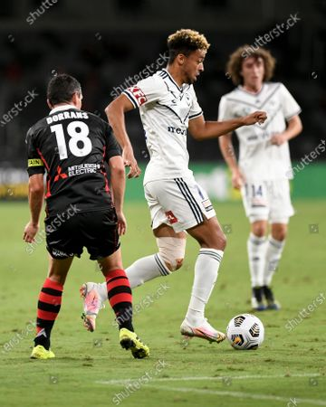 Ben Folami of Melbourne Victory runs past Graham Dorrans of Western Sydney Wanderers; Bankwest Stadium, Parramatta, New South Wales, Australia; A League Football, Western Sydney Wanderers versus Melbourne Victory.