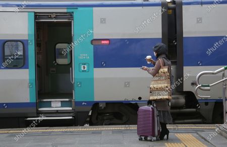 A woman prepares to board a train to go their hometown, in preparation for the traditional Korean holiday of Lunar New Year, at the Seoul station in Seoul, South Korea, 10 February 2021 ahead of the Lunar New Year's holiday, which falling from 11 to 14 February 2021. Lunar New Year is one of Korea's major traditional holidays. Many Koreans, during the festivities, will take long trips to their hometowns to visit family and pay homage to their ancestors.