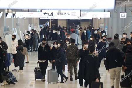 Stock Picture of People prepare to board a plane to go their hometown in preparation for the traditional Korean holiday of Lunar New Year at the Kimpo airport in Seoul, South Korea, 10 February 2021 ahead of the Lunar New Year's holiday, which falling from 11 to 14 February 2021. Lunar New Year is one of Korea's major traditional holidays. Many Koreans, during the festivities, will take long trips to their hometowns to visit family and pay homage to their ancestors.