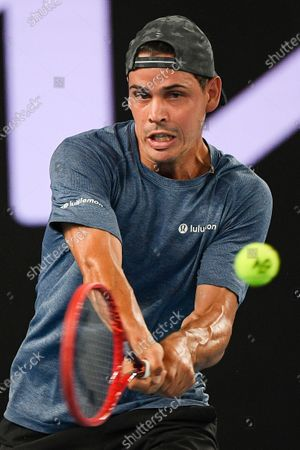 Australia's Alex Bolt akes a forehand return to Buglaria's Grigor Dimitrov during their second round match at the Australian Open tennis championship in Melbourne, Australia