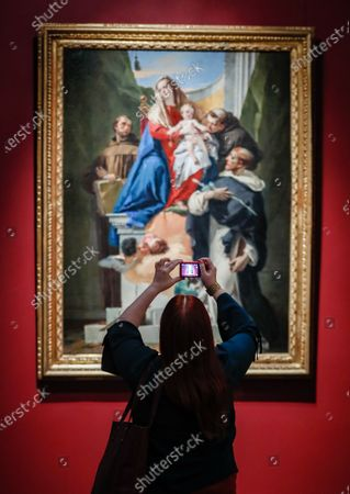 A visitor takes pictures of the painting 'Madonna with Saint Ludovic of Toulouse, Saint Antonio of Padua and Saint Francis of Assisi' by 18th-century Italian artist Giambattista Tiepolo during a press preview of the exhibition 'The Moscow Life of Giambattista Tiepolo and His Son Giandomenico' at the Pushkin State Museum of Fine Arts in Moscow, Russia 10 February 2021. The exhibition will run from 11 February to 01 November 2021.