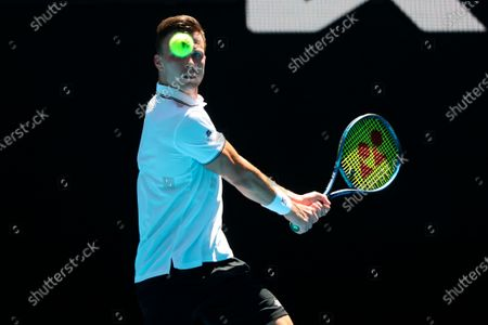 Hungary's Marton Fucsovics makes a backhand return to Switzerland's Stan Wawrinka during their match at the Australian Open Tennis championships in Melbourne, Australia