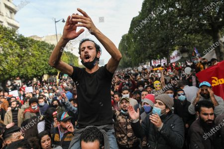 A young man sitting on the shoulders of a protester gestures as he shouts anti-government slogans during a rally held on avenue Habib Bourguiba in the capital Tunis in commemoration of the 8th anniversary of the assassination of the leftist opposition politician Chokri Belaid to call for uncovering the truth about the assassination of Chokri Belaid.Demonstrators also protested against police repression and demanded the release of young people arrested by the security forces. Some young protesters called for the decriminalization of Cannabis and soft drugs, and some others called for the fall of the government of the Prime Minister Hichem Mechichi and chanted slogans against Rached Ghannouchi, the president of the Islamist party Ennahda.