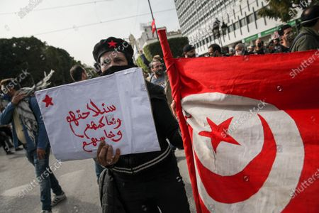 A female protester holds a placard with the red star that reads in Arabic, 'we will pursue you, judge you and hold you accountable' as she holds the flag of Tunisia during a rally held in the capital Tunis in commemoration of the 8th anniversary of the assassination of the leftist opposition politician Chokri Belaid to call for uncovering the truth about the assassination of Chokri Belaid.Demonstrators also protested against police repression and demanded the release of young people arrested by the security forces. Some young protesters called for the decriminalization of Cannabis and soft drugs, and some others called for the fall of the government of the Prime Minister Hichem Mechichi and chanted slogans against Rached Ghannouchi, the president of the Islamist party Ennahda.