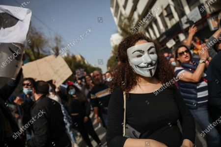 A Tunisian female protester wearing anonymous mask, during a march held towards avenue Habib Bourguiba in the capital Tunis in commemoration of the 8th anniversary of the assassination of the leftist opposition politician Chokri Belaid to call for uncovering the truth about the assassination of Chokri Belaid.Demonstrators also protested against police repression and demanded the release of young people arrested by the security forces. Some young protesters called for the decriminalization of Cannabis and soft drugs, and some others called for the fall of the government of the Prime Minister Hichem Mechichi and chanted slogans against Rached Ghannouchi, the president of the Islamist party Ennahda.