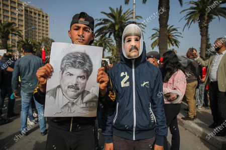 A young protester wears a mask of Chokri Belaid as another holds a portrait of Mohamed Brahmi (A Tunisian opponent assassinated in 2013) during a rally held in the capital Tunis in commemoration of the 8th anniversary of the assassination of the leftist opposition politician Chokri Belaid to call for uncovering the truth about the assassination of Chokri Belaid.Demonstrators also protested against police repression and demanded the release of young people arrested by the security forces. Some young protesters called for the decriminalization of Cannabis and soft drugs, and some others called for the fall of the government of the Prime Minister Hichem Mechichi and chanted slogans against Rached Ghannouchi, the president of the Islamist party Ennahda.