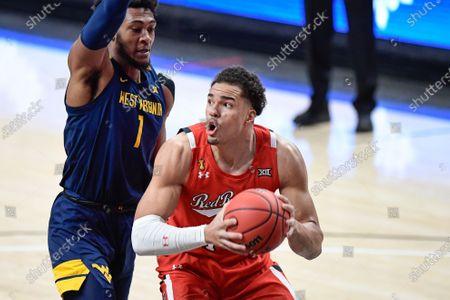 Texas Tech's Marcus Santos-Silva (14) controls the ball against West Virginia's Emmitt Mathews Jr. (11) during the first half of an NCAA college basketball game in Lubbock, Texas