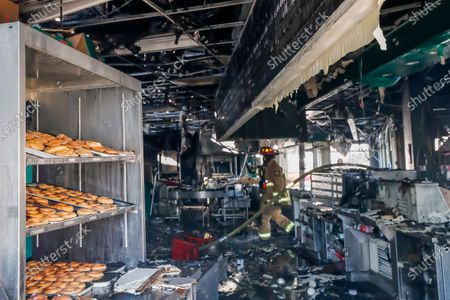 An Atlanta Fire Rescue firefighter surveys the damage inside the historic Krispy Kreme Doughnuts after an overnight fire destroyed the iconic restaurant in Atlanta, Georgia, USA, 10 February 2021. The 60-year-old Atlanta institution was purchased by NBA Hall of Famer Shaquille O'Neal in 2016. No injuries were reported in the Krispy Kreme fire, which was open at the time.