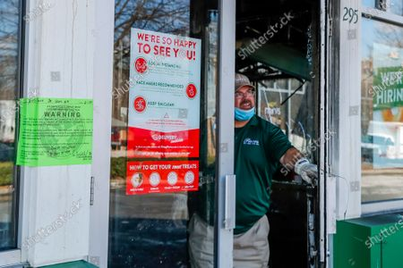 Stock Image of An employee of a fire restoration company attempts to lock the front door of the severely damaged, historic Krispy Kreme Doughnuts after an overnight fire destroyed the iconic restaurant in Atlanta, Georgia, USA, 10 February 2021. The 60-year-old Atlanta institution was purchased by NBA Hall of Famer Shaquille O'Neal in 2016. No injuries were reported in the Krispy Kreme fire, which was open at the time.