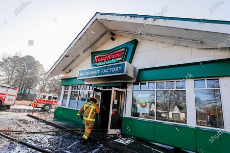 An Atlanta Fire Rescue firefighter walks inside the severely damaged historic Krispy Kreme Doughnuts after an overnight fire destroyed the iconic restaurant in Atlanta, Georgia, USA, 10 February 2021. The 60-year-old Atlanta institution was purchased by NBA Hall of Famer Shaquille O'Neal in 2016. No injuries were reported in the Krispy Kreme fire, which was open at the time.