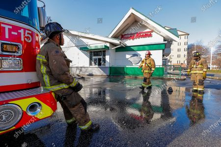 An Atlanta Fire Rescue firefighters survey the damage outside the historic Krispy Kreme Doughnuts after an overnight fire destroyed the iconic restaurant in Atlanta, Georgia, USA, 10 February 2021. The 60-year-old Atlanta institution was purchased by NBA Hall of Famer Shaquille O'Neal in 2016. No injuries were reported in the Krispy Kreme fire, which was open at the time.