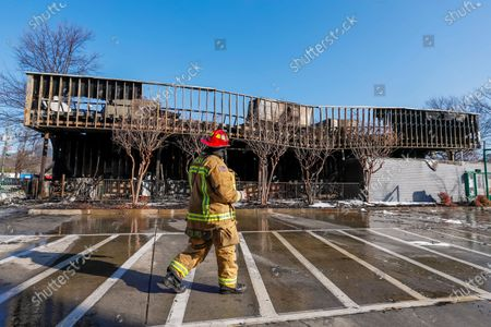 An Atlanta Fire Rescue firefighter surveys the damage outside the historic Krispy Kreme Doughnuts after an overnight fire destroyed the iconic restaurant in Atlanta, Georgia, USA, 10 February 2021. The 60-year-old Atlanta institution was purchased by NBA Hall of Famer Shaquille O'Neal in 2016. No injuries were reported in the Krispy Kreme fire, which was open at the time.