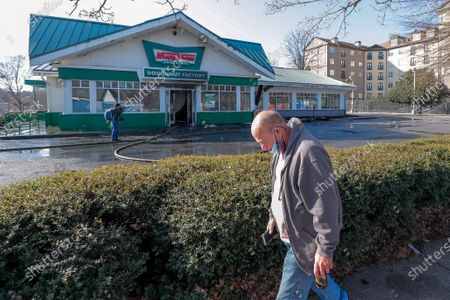 Passersby survey the damage outside the historic Krispy Kreme Doughnuts after an overnight fire destroyed the iconic restaurant in Atlanta, Georgia, USA, 10 February 2021. The 60-year-old Atlanta institution was purchased by NBA Hall of Famer Shaquille O'Neal in 2016. No injuries were reported in the Krispy Kreme fire, which was open at the time.