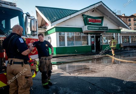Firefighters talk in front of a burned Krispy Kreme Doughnuts store in Atlanta on . The historic store was engulfed in flames early Wednesday. The store owned by Basketball Hall-of-Famer Shaquille O'Neal was significantly damaged