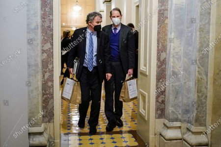 Sen. Sherrod Brown, D-Ohio and Sen. Ron Wyden, D-Or., walk the halls during a break in the second impeachment trial of former President Donald Trump, at the Capitol, in Washington