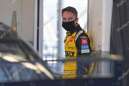 Christopher Bell waits in his garage before the start of a NASCAR Daytona 500 auto race practice session at Daytona International Speedway, in Daytona Beach, Fla