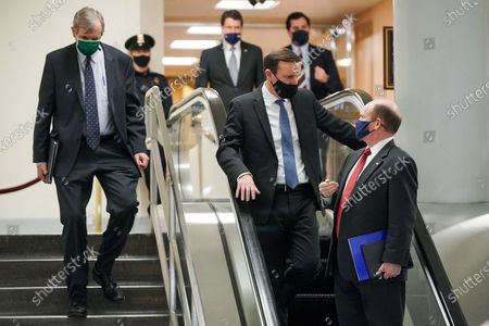 Sen. Christopher A. Coons (D-Del.), far right, speaks to Sen. Chris Murphy (D-Conn.), second toright, as they leave the Capitol after the second day of the impeachment trial of former President Donald Trump