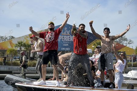 Tampa Bay Buccaneers NFL football tight end Tanner Hudson left, wide receiver Mike Evans, middle, and wide receiver Scott Miller celebrate their Super Bowl 55 victory over the Kansas City Chiefs with a boat parade in Tampa, Fla