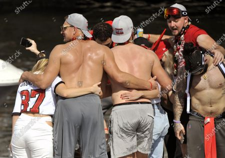 Tampa Bay Buccaneers' Rob Gronkowski (L) celebrates their win over the Kansas City Chiefs in Super Bowl LV during a boat parade down the Hillsborough River in Tampa