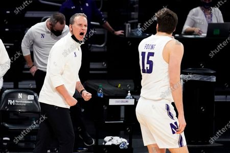 Northwestern coach Chris Collins, left, yells to center Ryan Young during the first half of the team's NCAA college basketball game against Indiana in Evanston, Ill