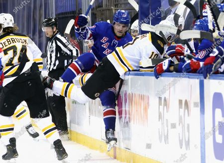 Boston Bruins Anders Bjork (10) and New York Rangers Alexis Lafreniere (13) collide during the first period of an NHL hockey game, in New York
