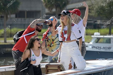 Ashli Evans, left, wife of Tampa Bay Buccaneers wide receiver Mike Evans, and Camille Kostek, girlfriend of tight end Rob Gronkowski, ride in a boat during a celebration of the Buccaneers Super Bowl 55 victory over the Kansas City Chiefs with a boat parade, in Tampa, Fla