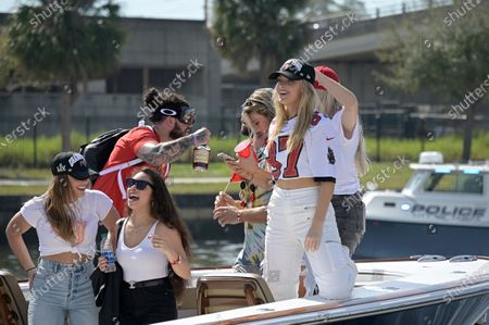 Ashli Evans, second from left, wife of Tampa Bay Buccaneers wide receiver Mike Evans, and Camille Kostek, girlfriend of tight end Rob Gronkowski, ride in a boat during a celebration of the Buccaneers Super Bowl 55 victory over the Kansas City Chiefs with a boat parade, in Tampa, Fla