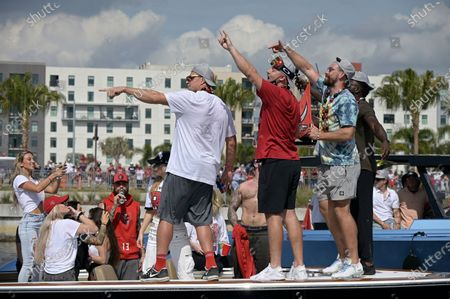 Stock Photo of Tampa Bay Buccaneers tight ends Rob Gronkowski, left, Tanner Hudson, center, and Cameron Brate acknowledge fans during a celebration of their Super Bowl 55 victory over the Kansas City Chiefs with a boat parade, in Tampa, Fla