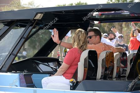 Tampa Bay Buccaneers quarterback Tom Brady waves from the console of his boat during a celebration of their Super Bowl 55 victory over the Kansas City Chiefs with a boat parade, in Tampa, Fla