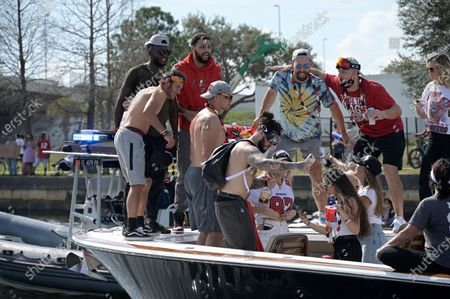 Tampa Bay Buccaneers receivers Chris Godwin, from left, Scotty Miller and Mike Evans and tight ends Rob Gronkowski, center, Cameron Brate and Tanner Hudson, right, pose for photos during a celebration of their Super Bowl 55 victory over the Kansas City Chiefs with a boat parade, in Tampa, Fla
