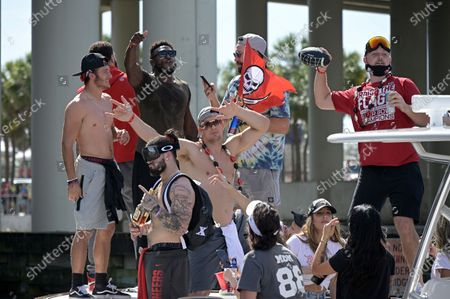 Stock Image of Tampa Bay Buccaneers players Scotty Miller, left, Chris Godwin, second from left, Rob Gronkowski, center, and Cameron Brate watch as Tanner Hudson, right, throws a football to a fan on a passing boat during a celebration of their Super Bowl 55 victory over the Kansas City Chiefs with a boat parade, in Tampa, Fla