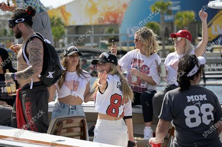 Camille Kostek, center, girlfriend of Tampa Bay Buccaneers tight end Rob Gronkowski, waves to fans during a celebration of their Super Bowl 55 victory over the Kansas City Chiefs with a boat parade, in Tampa, Fla