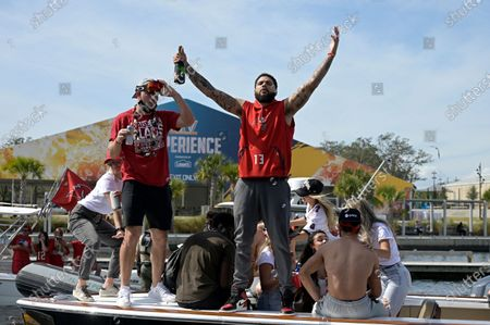 Tampa Bay Buccaneers receiver Mike Evans, center, and Tanner Hudson, left, celebrate on a boat during a celebration of their Super Bowl 55 victory over the Kansas City Chiefs with a boat parade, in Tampa, Fla