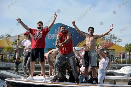 Tampa Bay Buccaneers receiver Mike Evans, center, and tight end Tanner Hudson, left, and receiver Scotty Miller celebrate on a boat during a celebration of their Super Bowl 55 victory over the Kansas City Chiefs with a boat parade, in Tampa, Fla