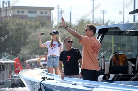 Tampa Bay Buccaneers quarterback Tom Brady waves to fans as his personal trainer Alex Guerrero, left, watches during a celebration of their Super Bowl 55 victory over the Kansas City Chiefs with a boat parade, in Tampa, Fla
