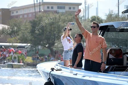 Tampa Bay Buccaneers quarterback Tom Brady, right, waves to fans as his personal trainer Alex Guerrero, center, watches during a celebration of their Super Bowl 55 victory over the Kansas City Chiefs with a boat parade, in Tampa, Fla