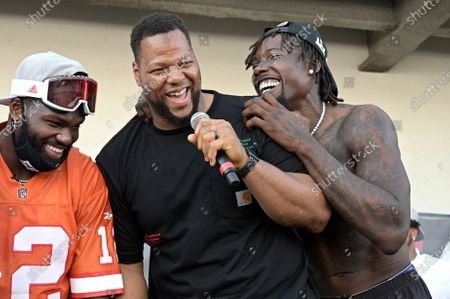 Stock Image of Tampa Bay Buccaneers defensive lineman Ndamukong Suh, center, and outside linebackers Shaquil Barrett, left, and Jason Pierre-Paul address the audience during a celebration of their Super Bowl 55 victory over the Kansas City Chiefs after taking part in a boat parade, in Tampa, Fla
