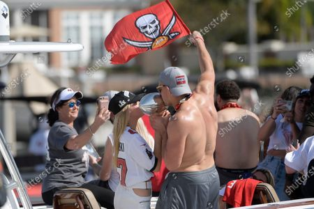 Tampa Bay Buccaneers tight end Rob Gronkowski, right, and Camille Kostek kiss the Vince Lombardi trophy during a celebration of their Super Bowl 55 victory over the Kansas City Chiefs with a boat parade, in Tampa, Fla