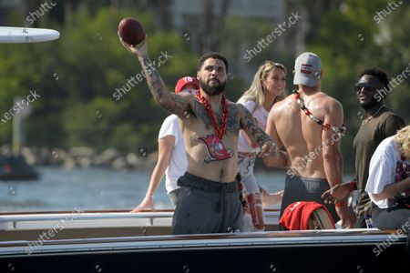 Tampa Bay Buccaneers wide receiver Mike Evans throws a football to a fan in a passing boat during a celebration of their Super Bowl 55 victory over the Kansas City Chiefs with a boat parade, in Tampa, Fla