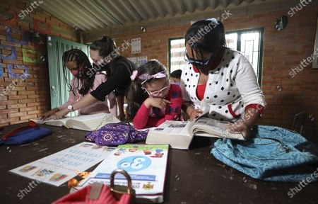 Stock Photo of Ana Milena Liberato, right, reads a book with her daughter Wendy Valeria, as they do her biology homework at Los Soches Rural Community Library in Los Soches, a small rural village on the outskirts of Bogota, Colombia, . Every month Liberato must allocate 50,000 pesos (approximately 15 dollars) to buy internet packages, although in the middle of the new coronavirus pandemic she lost her job