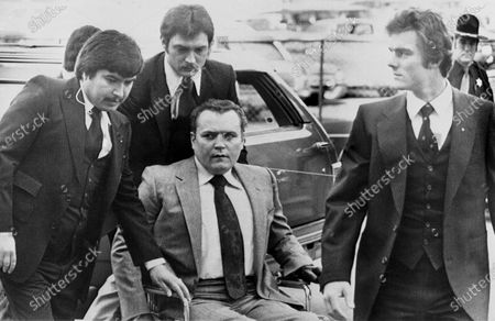 """Stock Image of Hustler"""" magazine publisher Larry Flynt is surrounded by heavy security as he arrives at the Fulton County Courthouse in Atlanta on March 19, 1979, for the start of his trial on obscenity charges. Flynt, who turned """"Hustler"""" magazine into an adult entertainment empire while championing First Amendment rights, has died at age 78. His nephew, Jimmy Flynt Jr., told The Associated Press that Flynt died, of heart failure at his Hollywood Hills home in Los Angeles"""