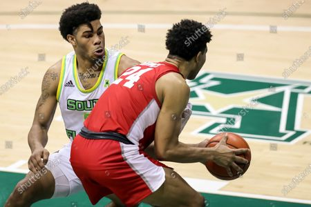 Houston's Quentin Grimes (24) drives against South Florida's David Collins during the second half of an NCAA college basketball game, in Tampa, Fla. Houston won 82-65
