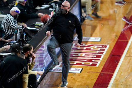 Wake Forest coach Steve Forbes celebrates after the team scored against Boston College during the second half of an NCAA basketball game, in Boston